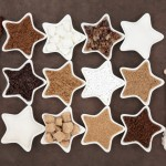 Brown and white sugar selection with crystal lollipops in abstract design over brown paper background.